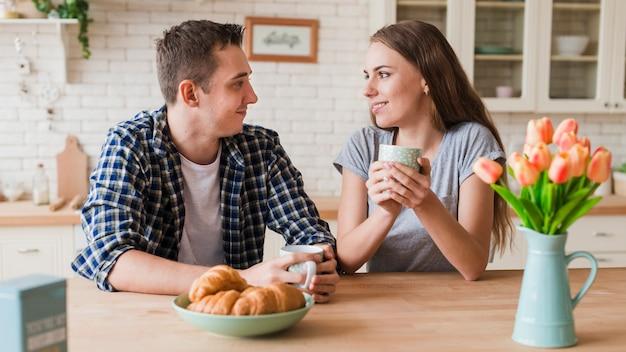ロマンチックなカップルはテーブルで休んでお茶をすすりながら