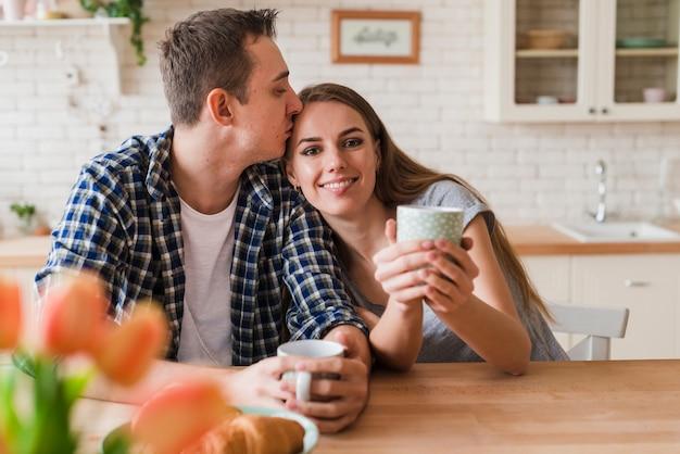 喜んでカップルがキスをし、テーブルでお茶を楽しんで