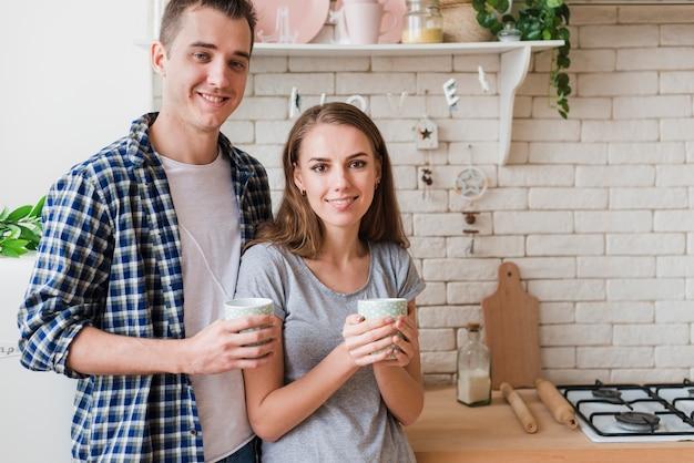 満足しているボンディングカップルが台所で休んで醸造を飲み