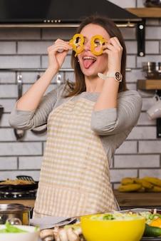 Женщина держит кусочки перца на глазах, показывая язык