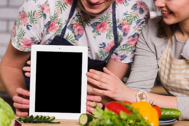 台所のテーブルにタブレットを保持している男と女