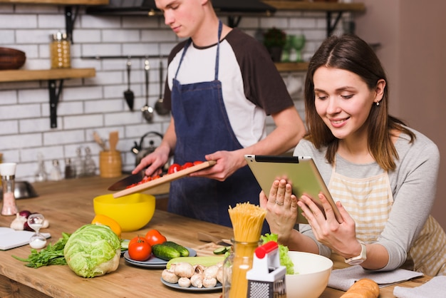 女性がタブレットを見ながらサラダを準備する男