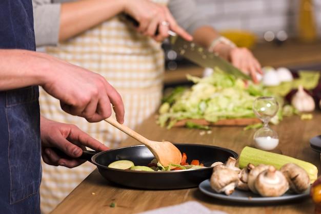 台所で野菜を調理するカップル