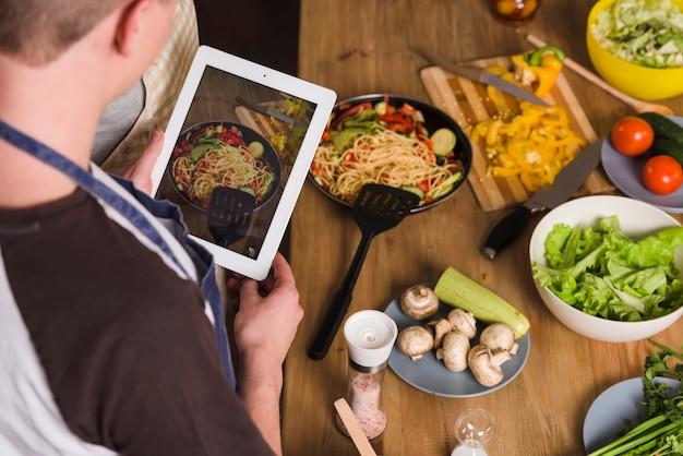 調理済みの料理の写真を撮る男