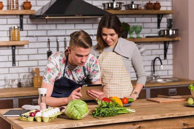 カップル料理や台所でタブレットを使用して