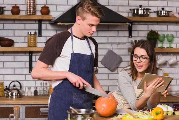 カボチャを調理し、タブレットを使用してカップル