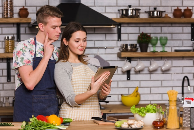 Молодая пара смотрит рецепт на планшете в кухне