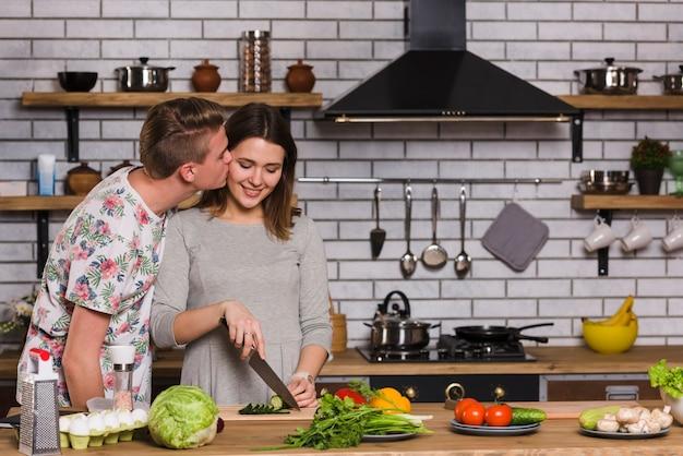 キッチンで料理のガールフレンドにキスをする男性