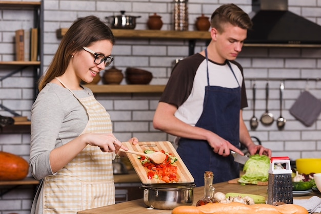 Улыбающаяся женщина готовит салат с парнем