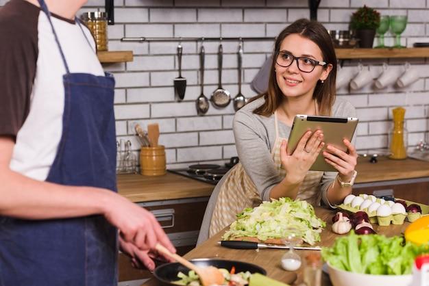 Молодая женщина смотрит на приготовления парня