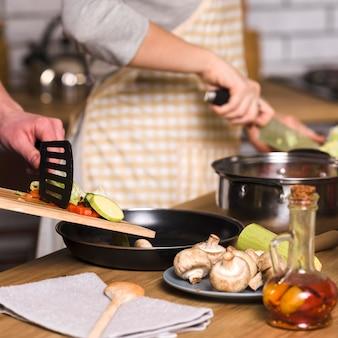 自宅で夕食のための料理を作るカップル