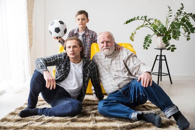 Мужчины смотрят футбол, сидя на ковре у себя дома