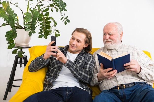 Сын показывает отцу информацию по телефону