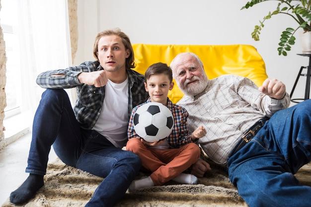 Счастливая семья из нескольких поколений сидит на полу вместе