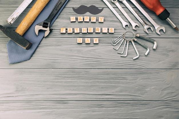 Инструменты возле декоративных усов с галстуком и счастливыми словами дня отца