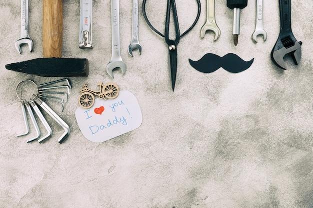 Коллекция инструментов возле декоративных усов со словами папа «я люблю тебя»