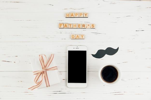 ギフトと一杯の飲み物を持つスマートフォンの近く幸せな父親の日言葉