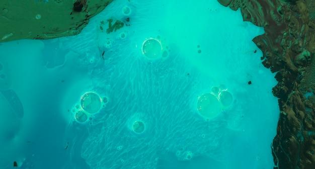 ターコイズブルーと緑色のペンキのテクスチャ背景の上の泡