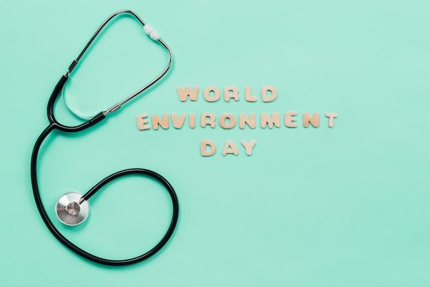 聴診器と単語環境日サインオン緑色の背景で