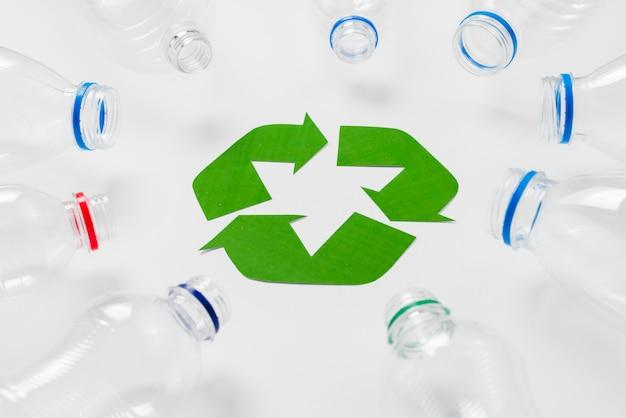 リサイクルのロゴの周りの空のペットボトル