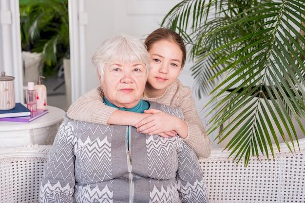 彼女の孫娘と一緒にポーズをとって高齢者のおばあちゃん