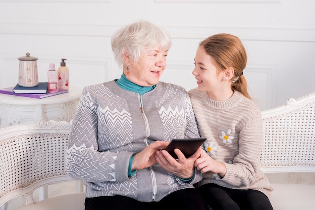 Пожилая бабушка читает с внучкой
