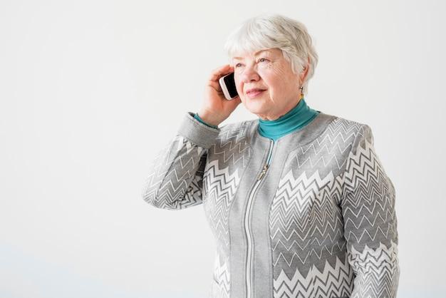 Пожилая бабушка разговаривает по телефону