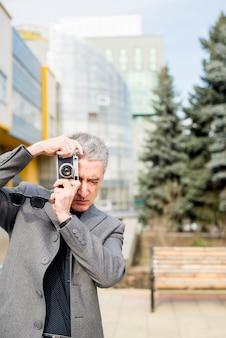 高齢者のビジネスマンが写真を撮る