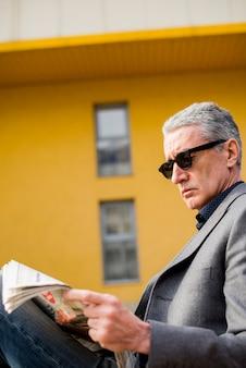 年配のビジネスマン読書新聞