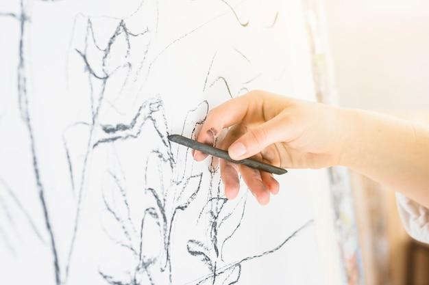 木炭で描く人間の手のクローズアップ