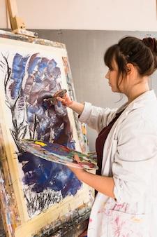 ペイントブラシでキャンバスに絵を描く若い女性