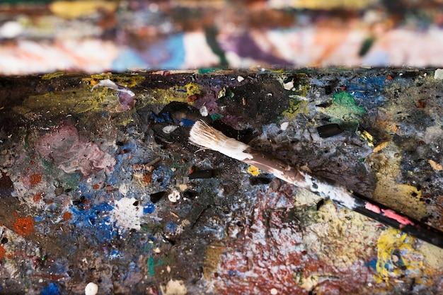 古い乱雑な混合色パレットと絵筆