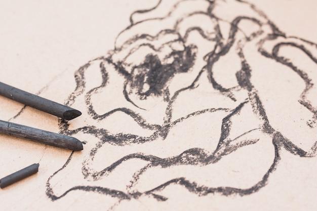 Черная угольная палочка художника с нечетким рисунком на простом фоне