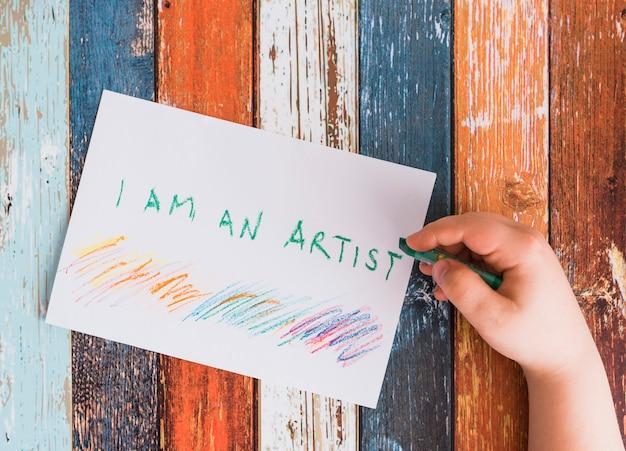 緑色のクレヨンと白い紙の上の「私は芸術家です」というテキストを書く人間の手のクローズアップ