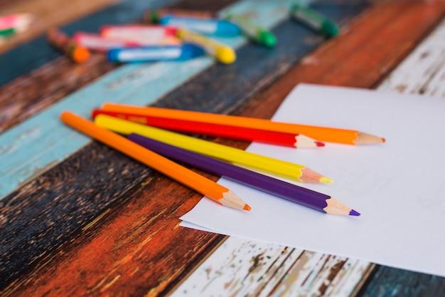 カラフルな鉛筆色と塗られた古いテーブルの上のホワイトペーパー