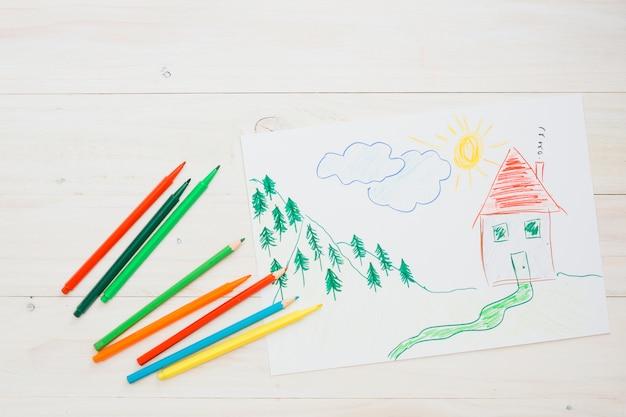 Нарисованная картина на белом листе с цветным карандашом над деревянной текстурой