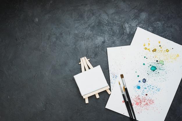 水彩画汚れ紙とミニイーゼルとペイントブラシの高角度のビュー
