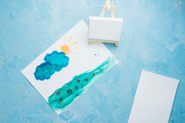 水彩画の背景にミニイーゼルで描かれた紙の絵を手します。