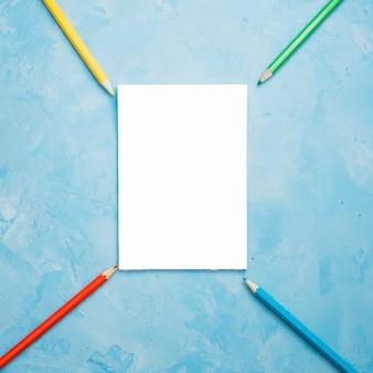青い織り目加工の表面に白い空白のカードとカラフルな鉛筆の配置