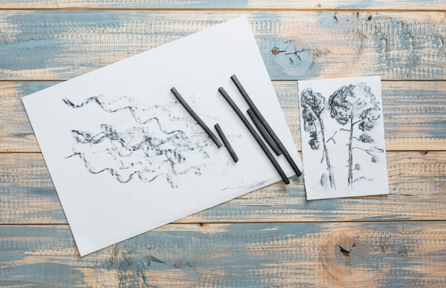 Рисованные бумага и художественные принадлежности угольной палочкой на деревянный стол