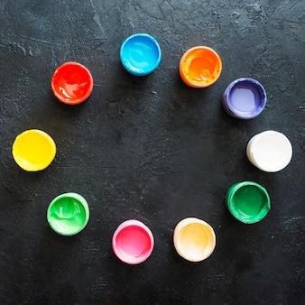 塗料容器は黒い表面に円形パターンで配置