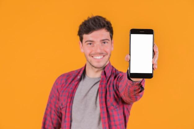 空白の白い画面携帯電話を示す笑みを浮かべて若い男の肖像