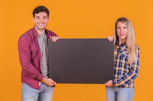 Портрет молодой пары, держащей пустой черный плакат на оранжевом фоне