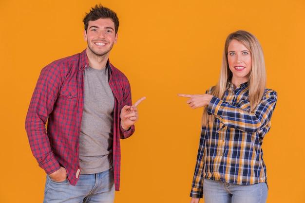 オレンジ色の背景に対してお互いに自分の指を指している若いカップルの肖像画