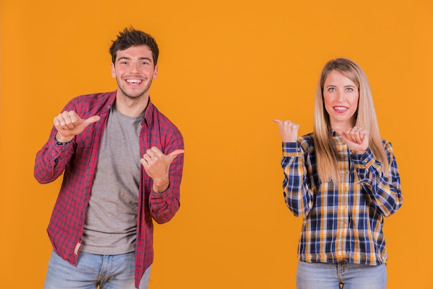 オレンジ色の背景に対してお互いに親指ジェスチャーを作る若いカップルの笑顔