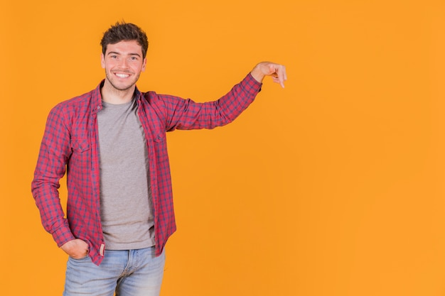 オレンジ色の背景に対して上向きに彼の指を指している若い男の笑みを浮かべてください。