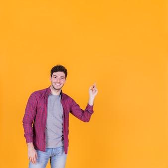 オレンジ色の背景に対して彼の指を指している幸せな若い男の肖像