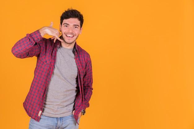 オレンジ色の背景に対して呼び出しジェスチャーを作る若い男のクローズアップ