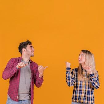 オレンジ色の背景に対して背中合わせに親指を示す若いカップルの肖像画