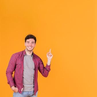 オレンジ色の背景に対して上向きに彼の指を指している笑顔の若い男のクローズアップ